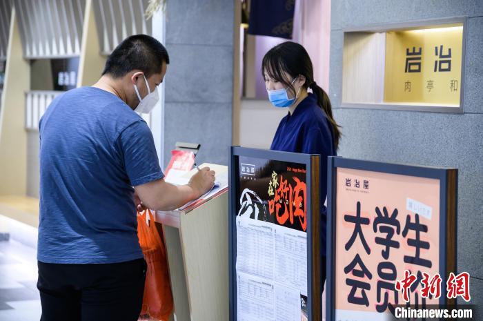 """岩冶屋日式烤肉店前张贴着""""中华人民共和国海关进口货物报关单""""。 李南轩 摄"""
